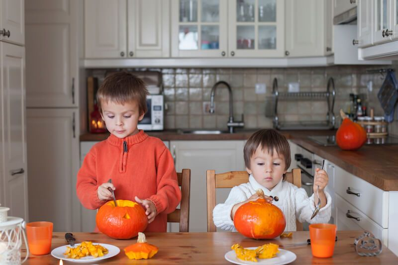 Two Little Boys Carving Pumpkins